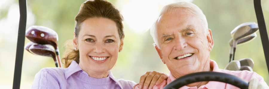 smiling couple with dentures in golf cart